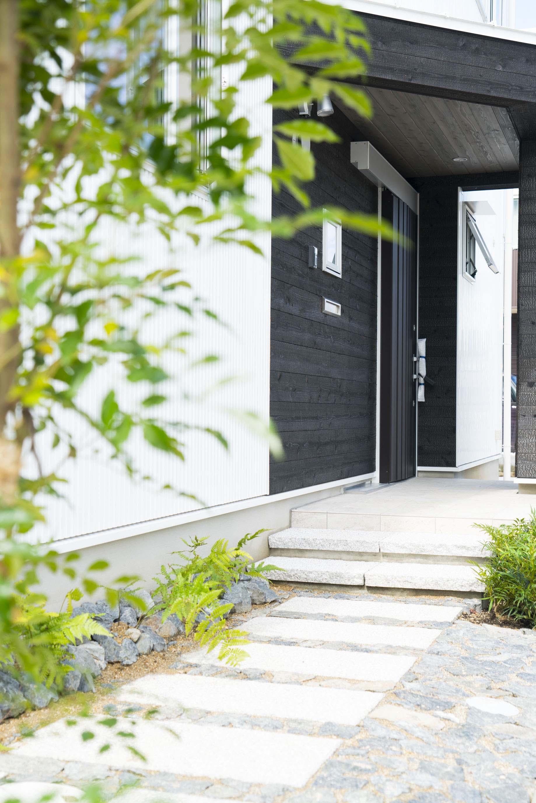 公園前の2世帯の住まいの部屋 石畳の玄関アプローチ