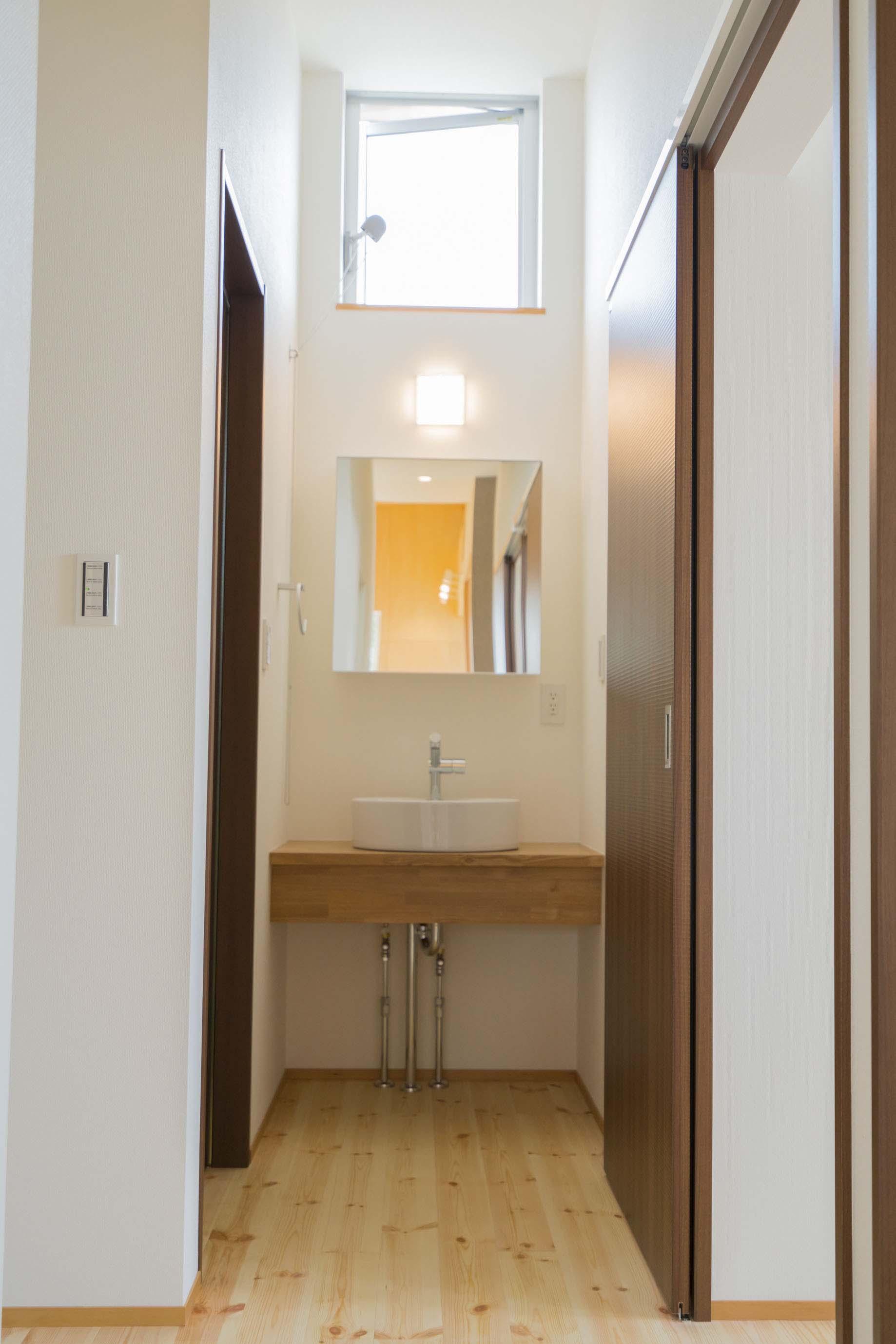 公園前の2世帯の住まいの部屋 シンプルな洗面台