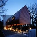 ゆるい傾斜地に建てられた逆さ舟型のフォルムの家