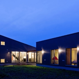 農村風景を望む母屋と並ぶ家 (屋根形状のシルエットが明快に浮かび上がる夕景)