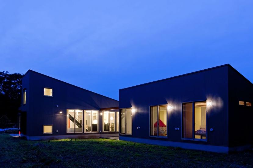 農村風景を望む母屋と並ぶ家の写真 屋根形状のシルエットが明快に浮かび上がる夕景