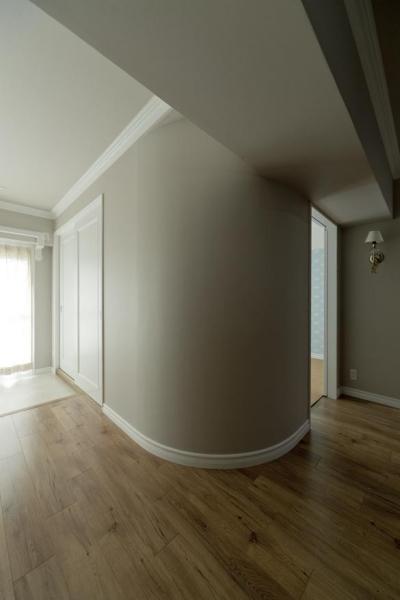 アールの壁 (モールディングとアースカラーの色使いが際立つ住まい)