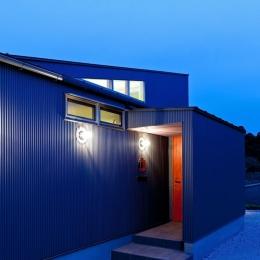 農村風景を望む母屋と並ぶ家 (玄関の木製戸にベンガラ塗料を塗った玄関回り近景.)