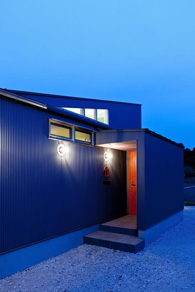 農村風景を望む母屋と並ぶ家の写真 玄関の木製戸にベンガラ塗料を塗った玄関回り近景.