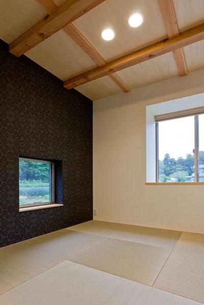 濃い色の和紙クロスを貼った縁なし畳を敷いた客間 (農村風景を望む母屋と並ぶ家)