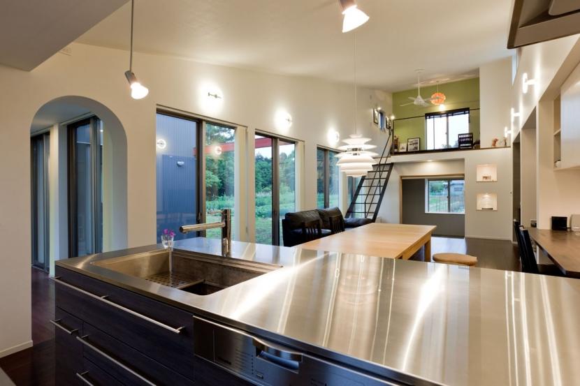 農村風景を望む母屋と並ぶ家の写真 アイランドキッチン(製作品)からリビング方面(吹き抜け)をみる