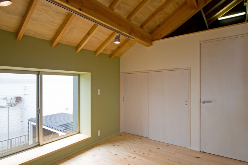 田園風景まっただ中の家の部屋 外壁面にモスグリーンのクロスを施工した2階の寝室