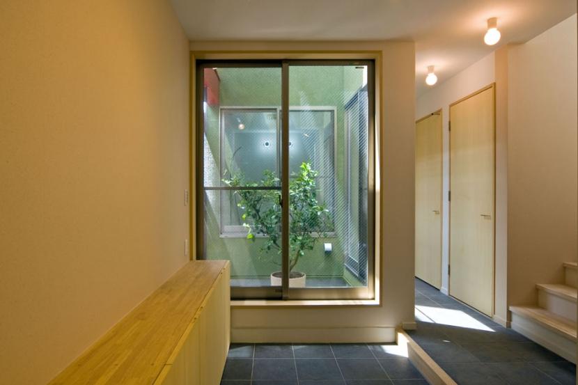 陽が降り注ぐライトコートのある家/東京都阿佐ヶ谷の家の写真 ライトコートに接する玄関の土間スペース