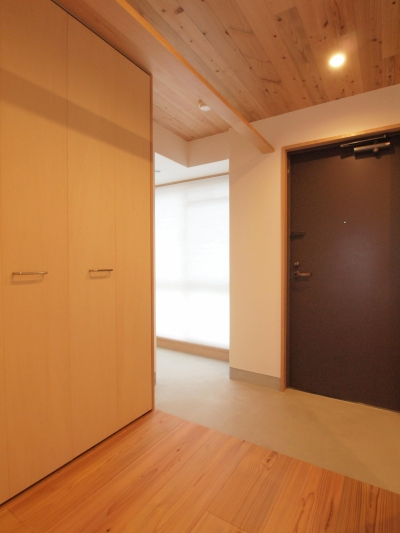 陽射しが差し込む明るい玄関土間 (土間スペースと小上がり寝室・床下収納のある木の住まい)