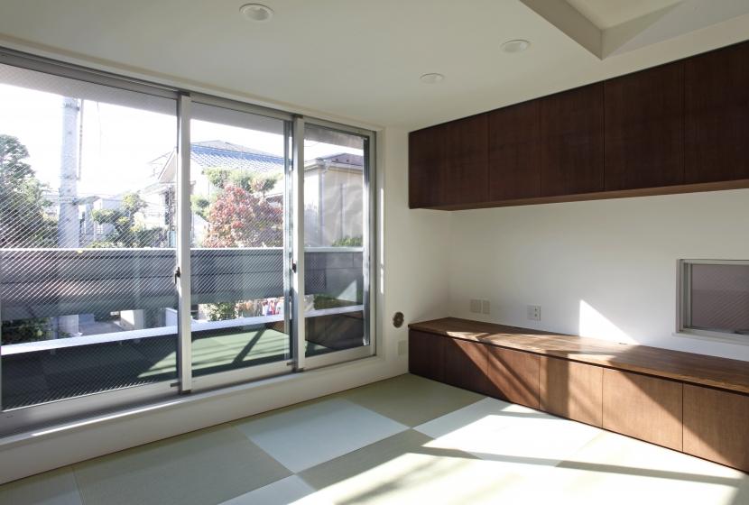 千駄木の家の部屋 2階居間_バルコニー越しに外の緑を見る