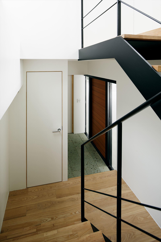 アカミネのいえの写真 柱と玄関と階段で構成された1F