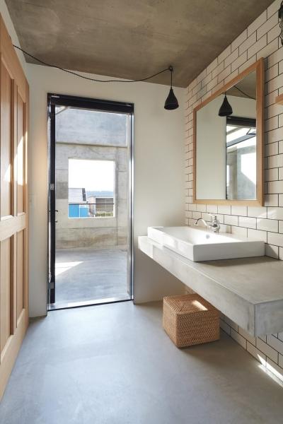 テラスと一体感のある洗面室 (森町の家 / インダストリアルデザインと自然を取り込むコンクリートハウス)