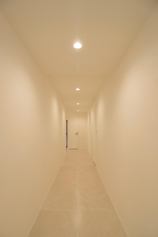 タイルと石材によるラグジュアリーリノベーション (廊下は扉の納まりを工夫してシームレスな空間へ)