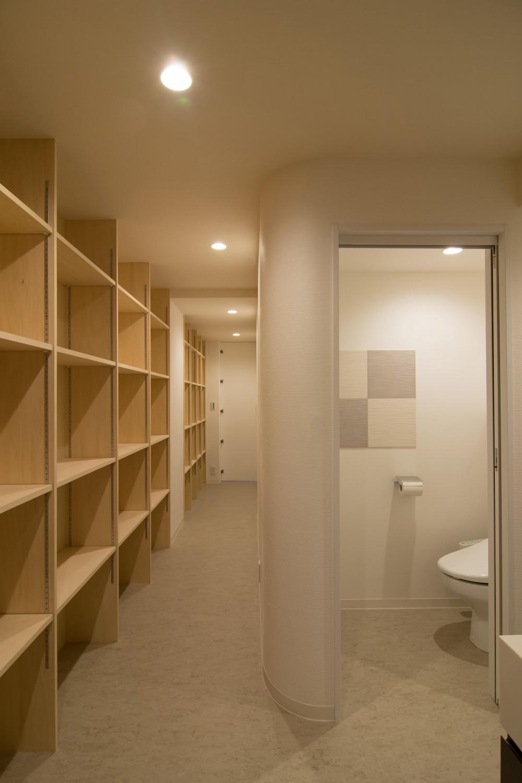 タイルと石材によるラグジュアリーリノベーション (バックヤードの廊下は壁一面に収納棚を設置)