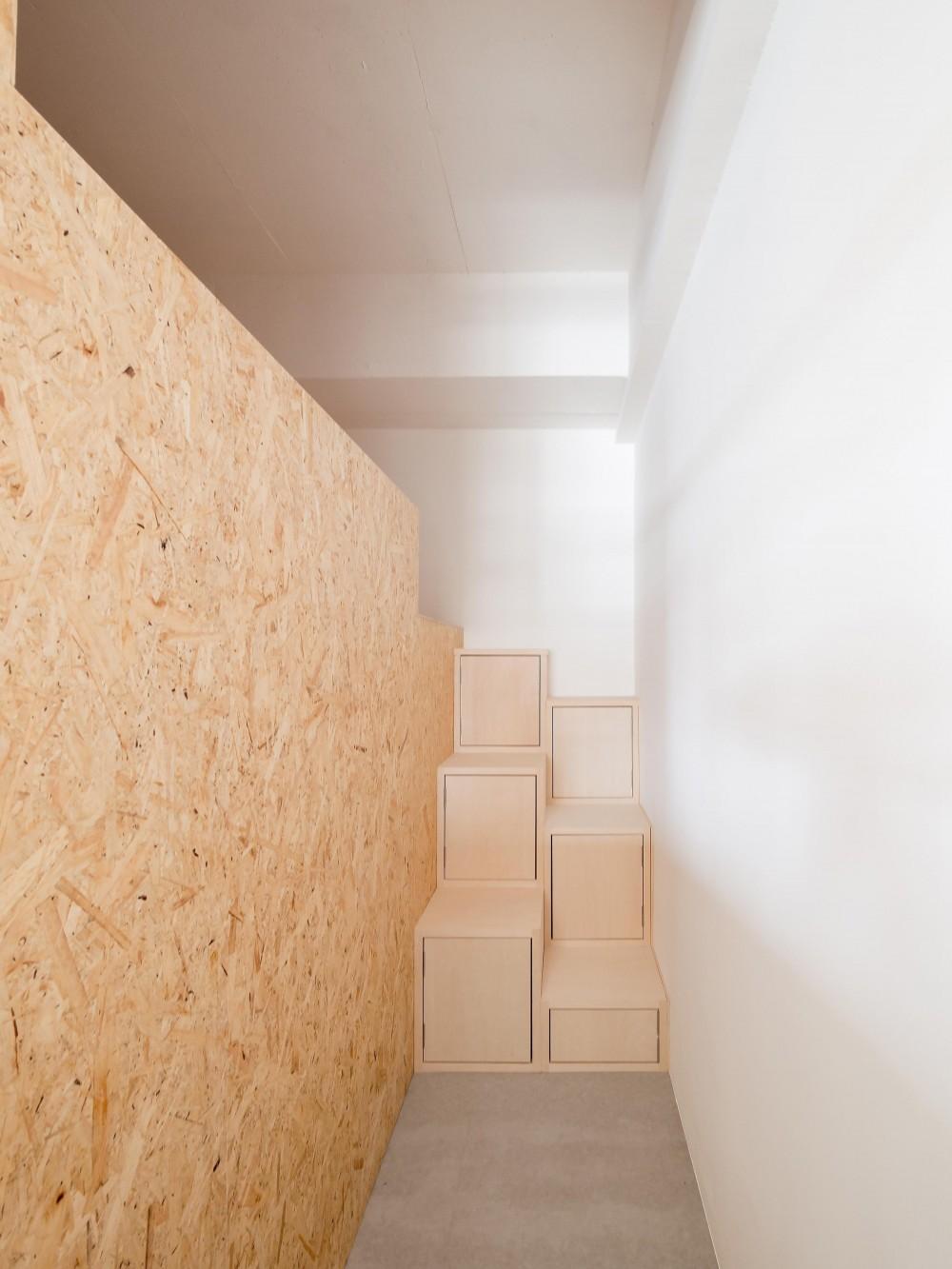 木とモノトーンの調和した家 (リズミカルなキッズベッドスペース上段への階段)