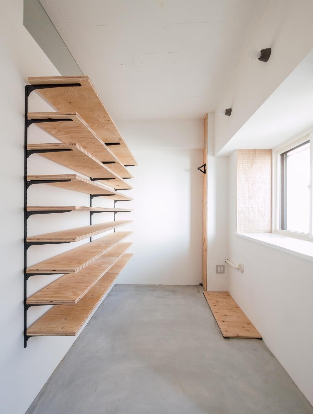 木とモノトーンの調和した家 (大容量収納の玄関土間)