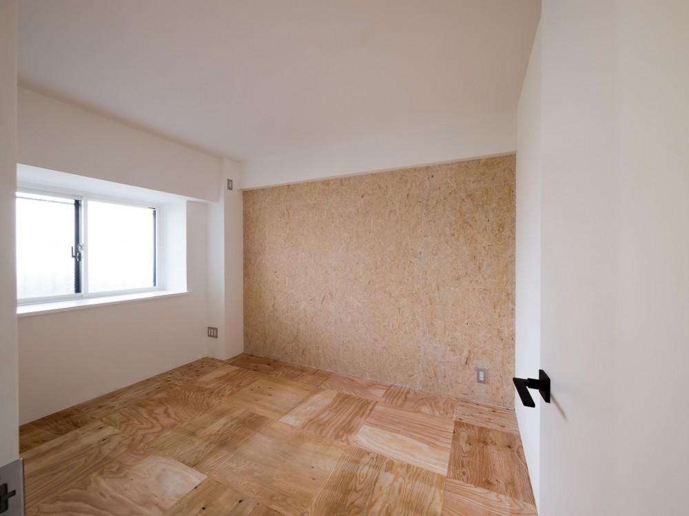 木とモノトーンの調和した家 (荒削りな雰囲気の床と壁の寝室)