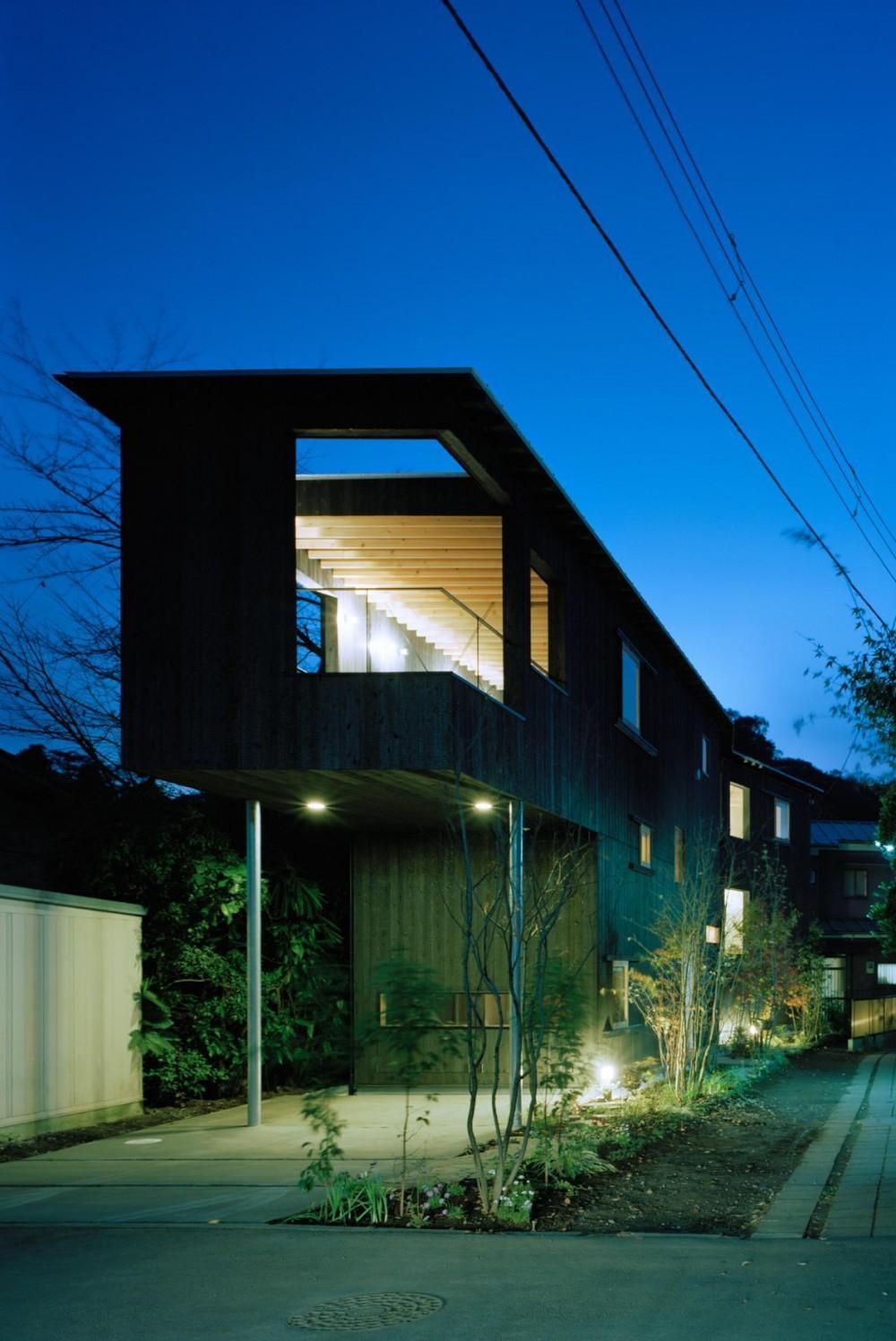 路地に沿う、北鎌倉の超細長い家 (路地に沿って曲がった焼杉の外観)