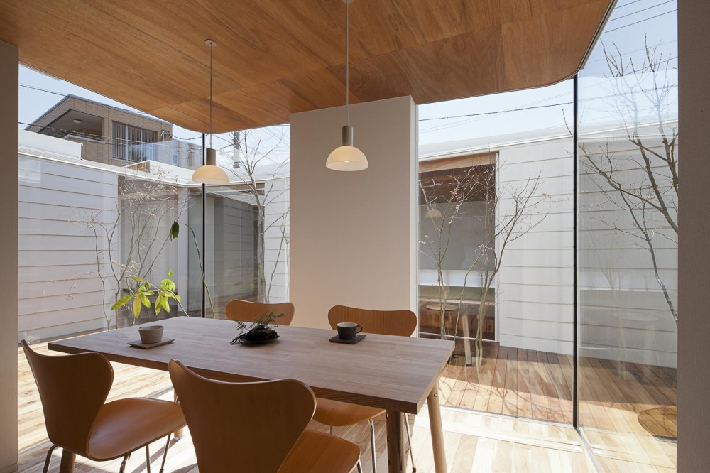 開放的な中庭デッキを包み込む平屋の家 (屋内と屋外が連続したダイニング)