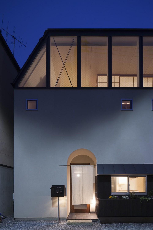 """""""のれん""""と立体図書館のある、東京の狭小、二世帯住宅 (夕景に浮かび上がる障子と暖簾のある外観)"""