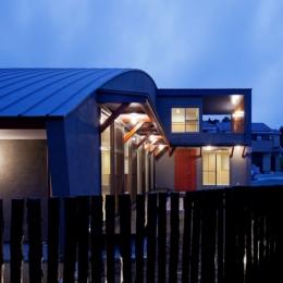(東京都あきる野市)武蔵増戸のR屋根の家 (木杭を利用した柵から光がもれる夕景)