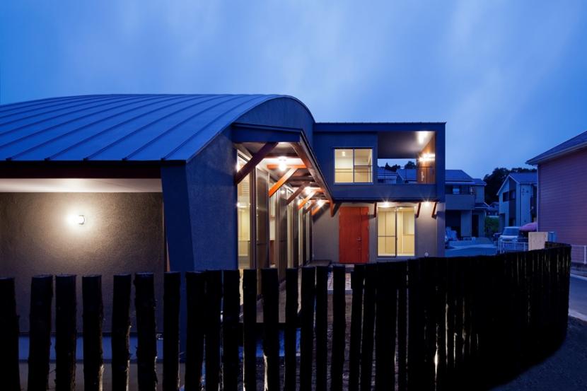 (東京都あきる野市)武蔵増戸のR屋根の家の部屋 木杭を利用した柵から光がもれる夕景