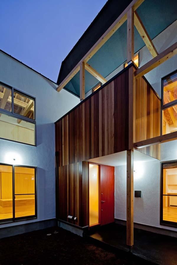 木格子の家/石神井台の二世帯住宅の写真 玄関および2階のバルコニーの外壁はセランカンバツ(木材)張り