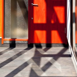 木格子の家/石神井台の二世帯住宅 (炭入りモルタルの床面とベンガラ塗装の玄関ドア)