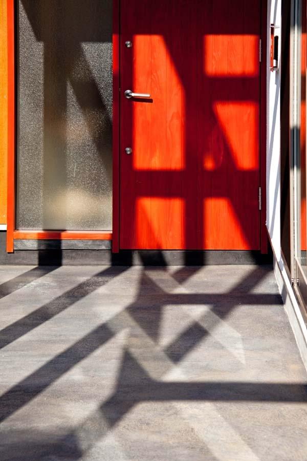 木格子の家/石神井台の二世帯住宅の部屋 炭入りモルタルの床面とベンガラ塗装の玄関ドア