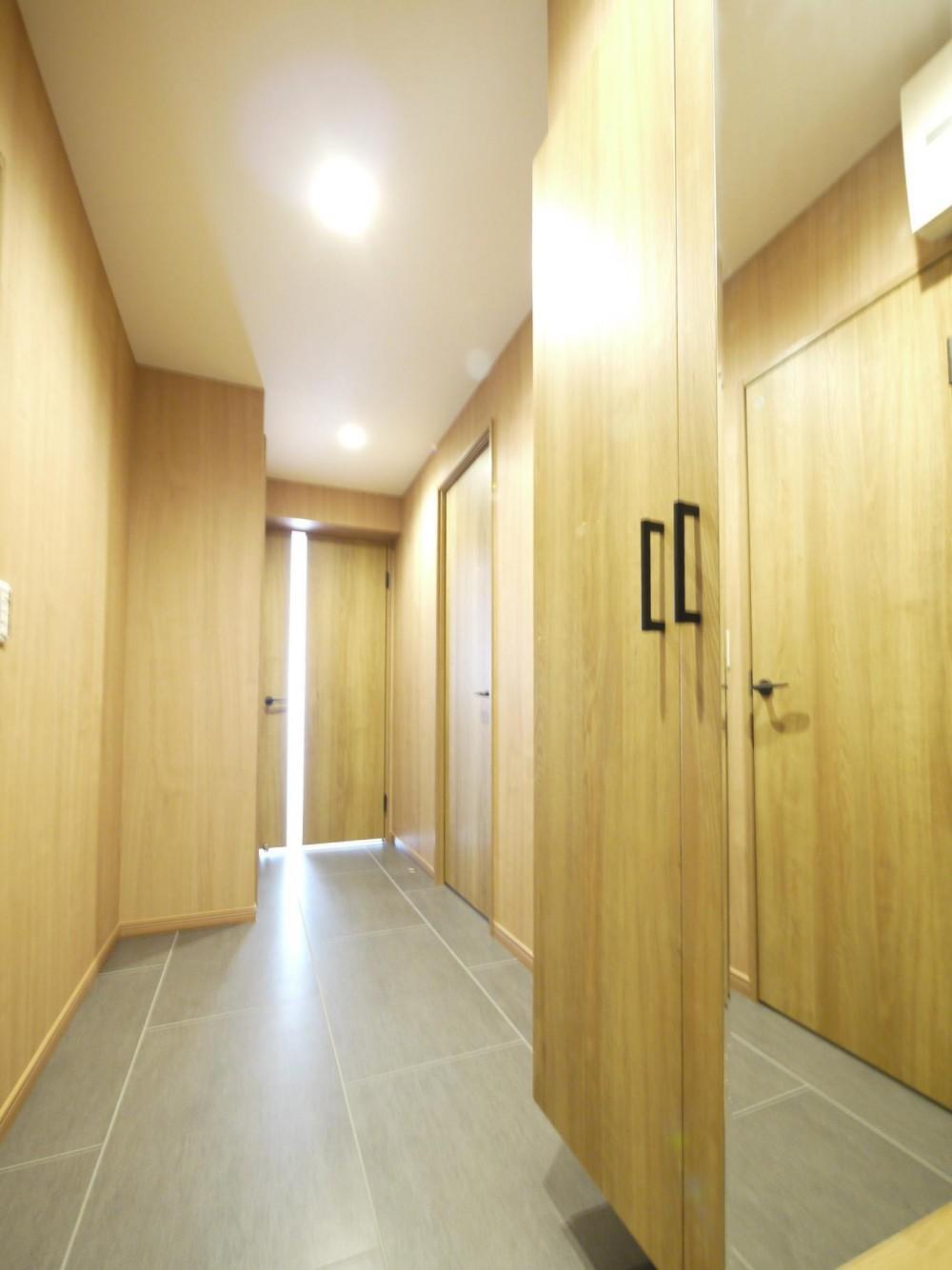 木目が映えるスタイリッシュキッチン (玄関)