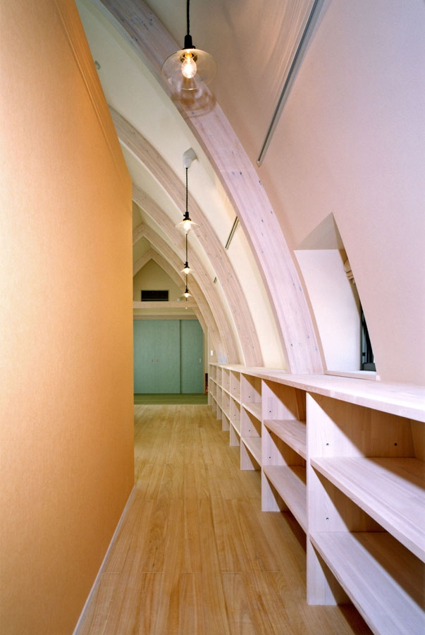 西熱海の陶芸工房のある家の部屋 オレンジにペイントされた壁側にキッチン.曲面側に陶器の展示ギャラリー