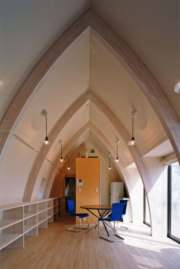 西熱海の陶芸工房のある家の部屋 骨格となる曲線の集成材の梁が特徴のリビング
