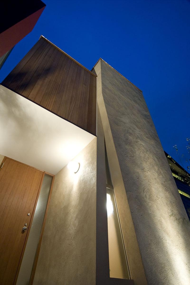 埼玉県和光市の区画整理地の家の写真 左官仕上とセランカンバツの木材が絡む玄関部分外観