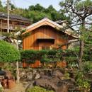 児島の小さなアトリエの写真 庭木越しに入口を見る