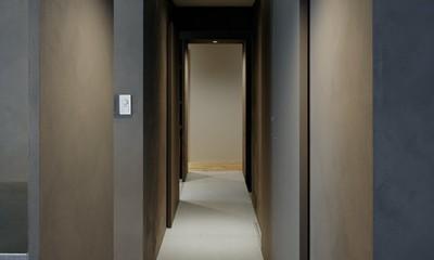 専用庭のある約100平米の団地リノベーション (リビングダイニングと個室をつなぐグレーに彩られた廊下)