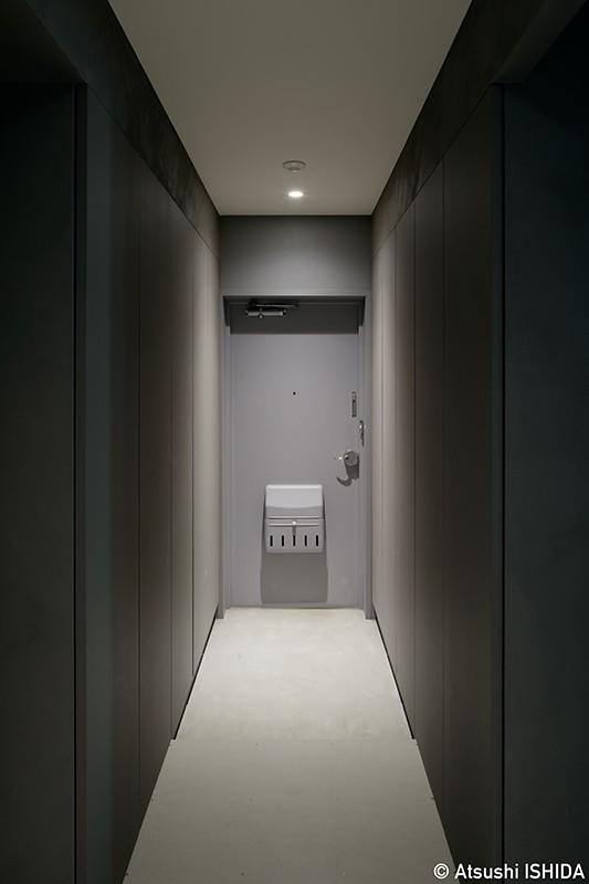 グレーが落ち着いた雰囲気をつくり出す玄関 (専用庭のある約100平米の団地リノベーション)