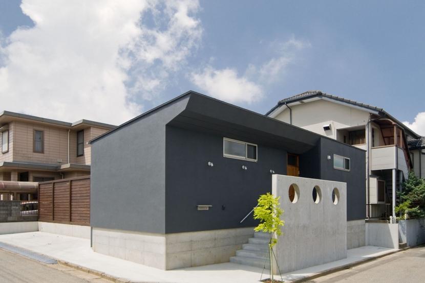 住宅地に建つコートハウス(通り抜け土間のある家)の部屋 コンクリート打っ放しの目隠し壁がアクセントとなっています