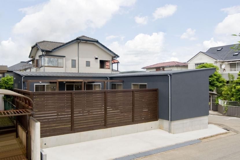 住宅地に建つコートハウス(通り抜け土間のある家)の部屋 コート(庭)を囲む木のスクリーン