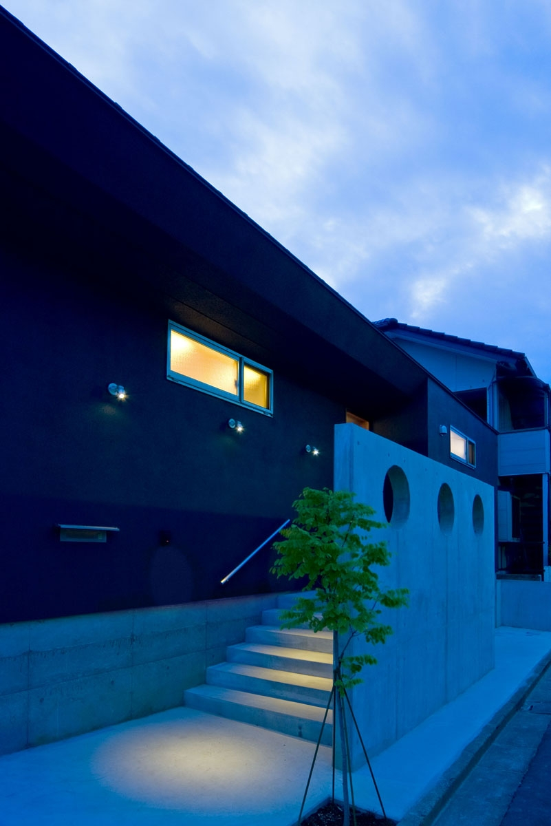 住宅地に建つコートハウス(通り抜け土間のある家)の部屋 シンボルツリーを植えたアプローチ空間