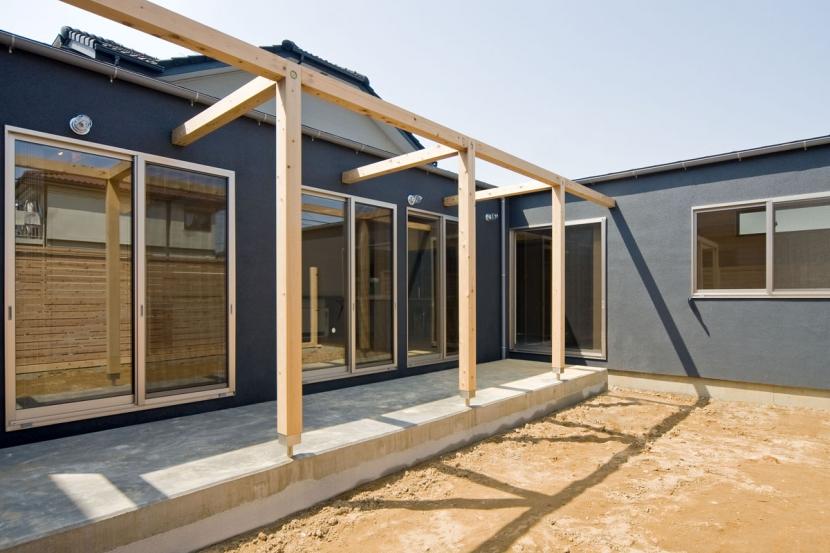 住宅地に建つコートハウス(通り抜け土間のある家)の部屋 木のフレームのかかるテラス