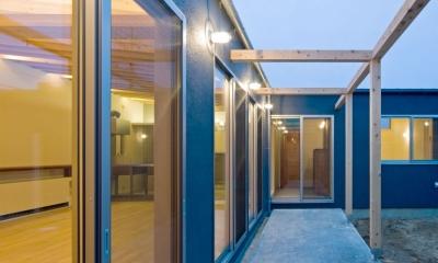 住宅地に建つコートハウス(通り抜け土間のある家) (室内とコート(中庭)の中間にある木のフレームのあるテラス)