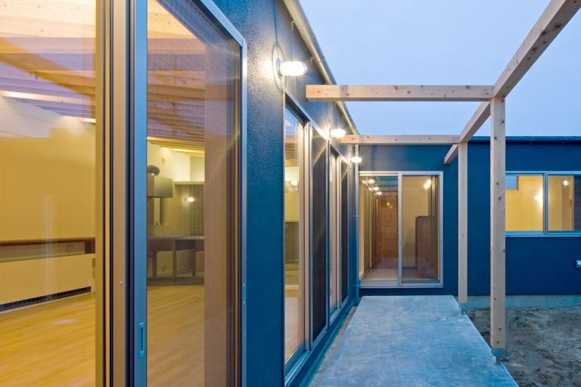 住宅地に建つコートハウス(通り抜け土間のある家)の部屋 室内とコート(中庭)の中間にある木のフレームのあるテラス