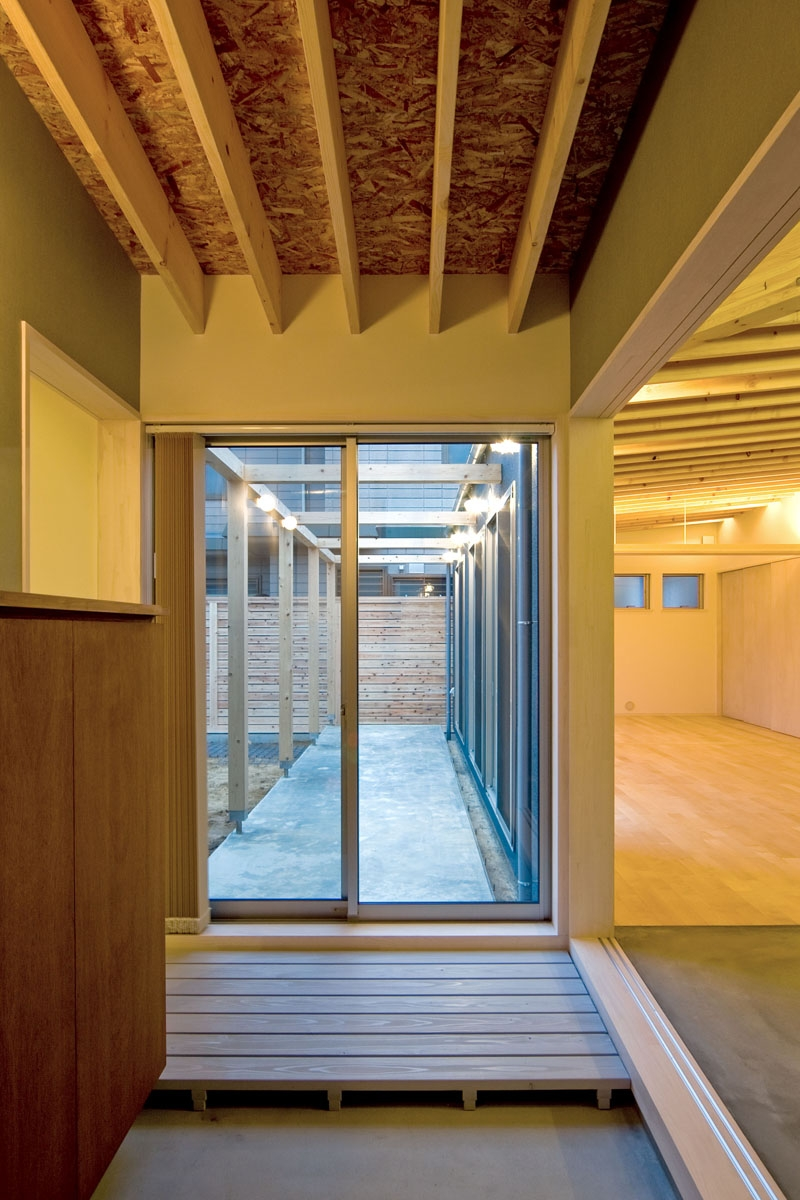 住宅地に建つコートハウス(通り抜け土間のある家)の部屋 玄関からコート(庭)に通り抜けられる土間
