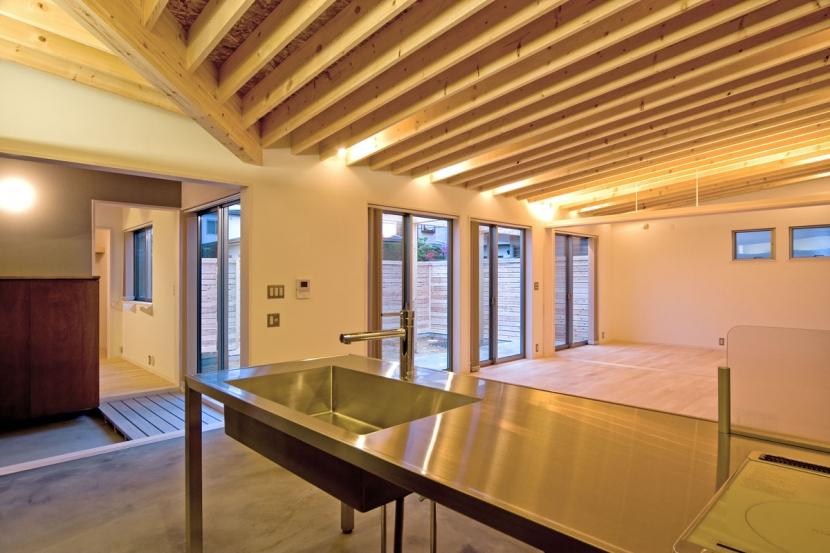 住宅地に建つコートハウス(通り抜け土間のある家)の部屋 シンプルさを追求したステンレス製のキッチン