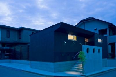 住宅地に建つコートハウス(通り抜け土間のある家) (3連の外灯とRC壁の3連の開口がアクセントの夕景)