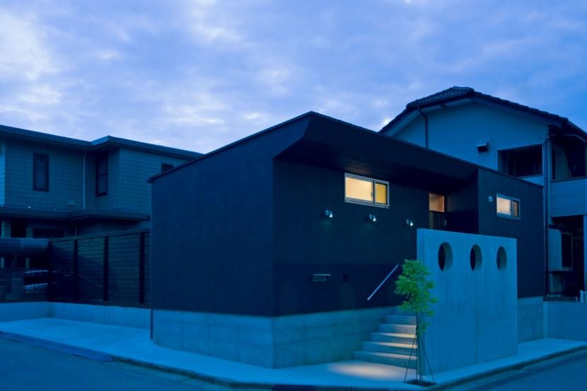 住宅地に建つコートハウス(通り抜け土間のある家)の部屋 3連の外灯とRC壁の3連の開口がアクセントの夕景