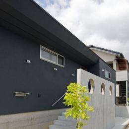 住宅地に建つコートハウス(通り抜け土間のある家) (玄関アプローチは目隠し兼用でRCの壁がアクセントとなっています.)