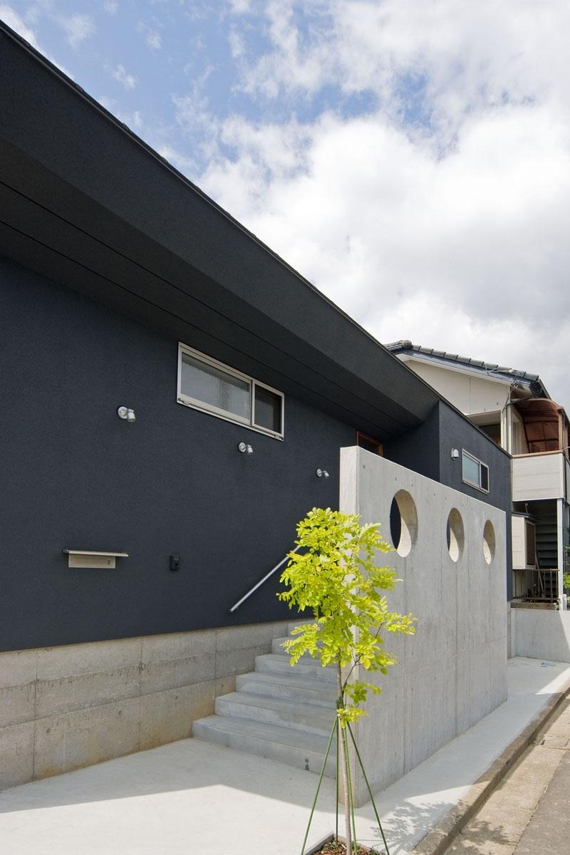 住宅地に建つコートハウス(通り抜け土間のある家)の部屋 玄関アプローチは目隠し兼用でRCの壁がアクセントとなっています.
