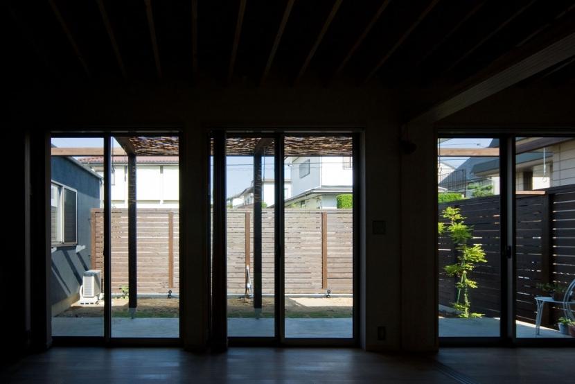 住宅地に建つコートハウス(通り抜け土間のある家)の部屋 リビングから庭(コート)を見る