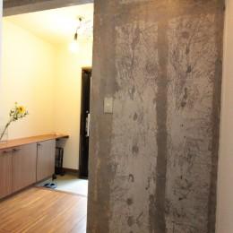 コンクリート躯体あらわしと、木材の素材感が味わいあるお住まい (玄関)